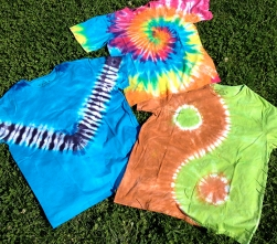 Three organic cotton tie dye t-shirts on grass.