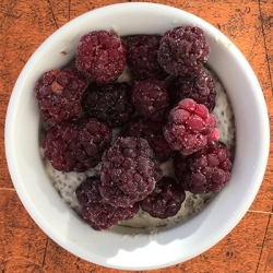 Picture of a dish of Coconut Chia-Seed Pudding with big blackberries on top.