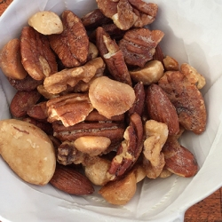 A picture of Paleo Maple-glazed Nuts in a white dish.